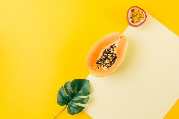 Una vista dall'alto di foglia artificiale; papaya e frutto della passione su carta bianca contro sfondo giallo
