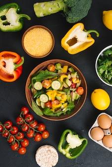Una vista dall'alto di insalata di verdure fresche; uova; torta di riso soffiato e polenta su sfondo di cemento nero