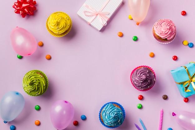 Una vista dall'alto di muffin; palloncini; gemme; confezione regalo e candele su sfondo rosa