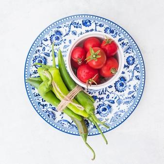 Una vista dall'alto di pomodori rossi e fascio di peperoncini verdi sul piatto in ceramica