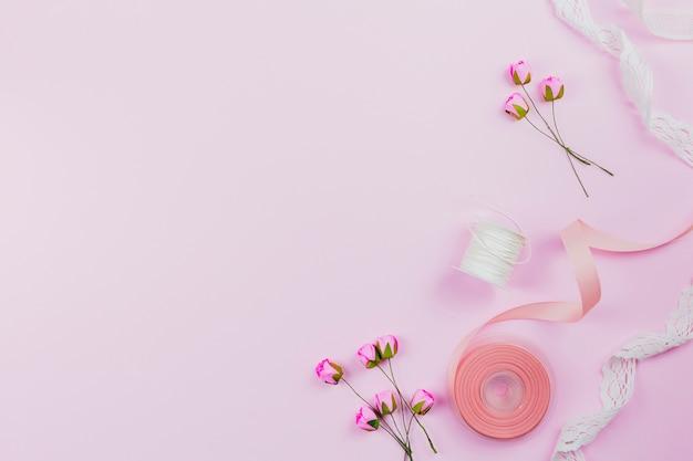 Una vista dall'alto di rose artificiali; bobina e nastri su sfondo rosa