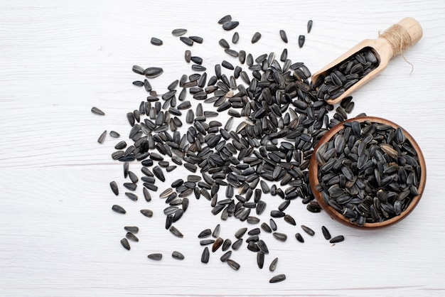 Una vista dall'alto di semi di girasole neri freschi e gustosi su tutto lo sfondo bianco granuli di semi di girasole