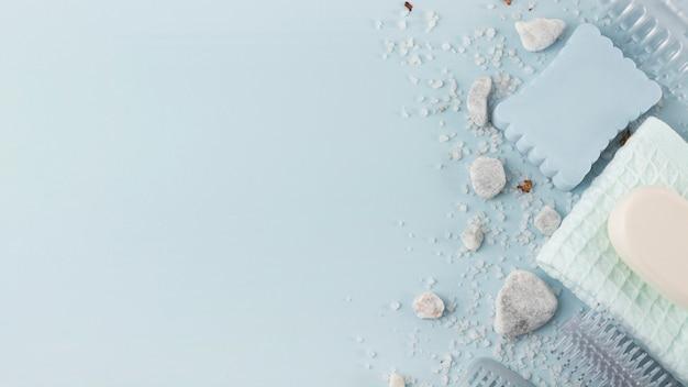 Una vista dall'alto di spugna; pietra termale; tovagliolo; sale e sapone su sfondo blu