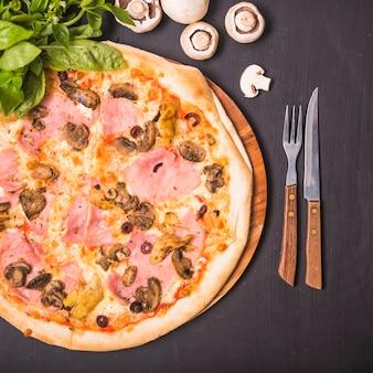 Una vista dall'alto di una deliziosa pizza fatta in casa con basilico e funghi