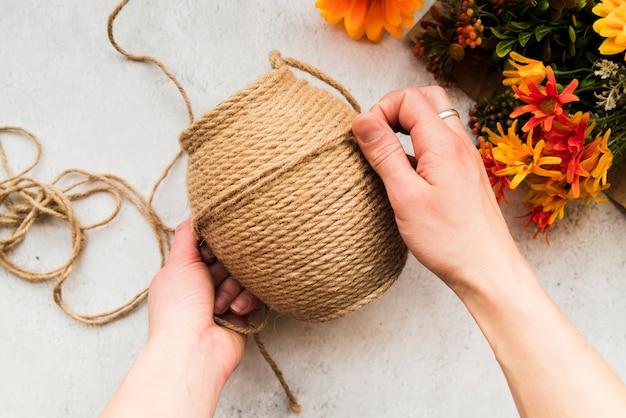 Una vista dall'alto di una donna che fa la stringa con corda di iuta su sfondo con texture