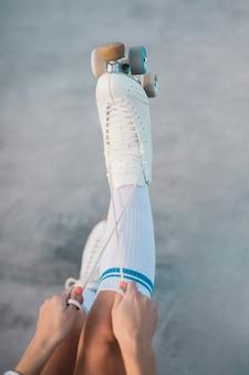Una vista dall'alto di una donna che lega il merletto del pattino a rotelle