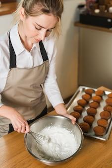 Una vista dall'alto di una donna che mescola la crema di uova bianche in una ciotola con la frusta