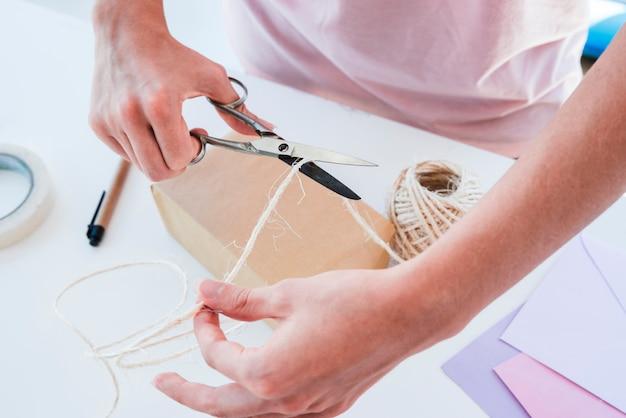 Una vista dall'alto di una donna che taglia il filo di iuta con le forbici sul tavolo