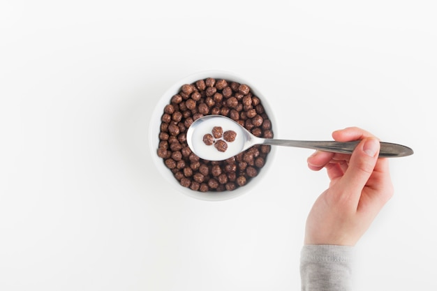 Una vista dall'alto di una mano femminile con cucchiaio con gustose palline di cereali al cioccolato e latte nella ciotola