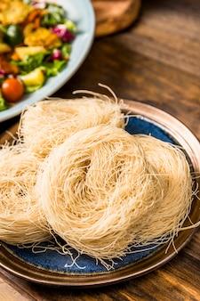 Una vista dall'alto di vermicelli di riso sul piatto sopra la scrivania