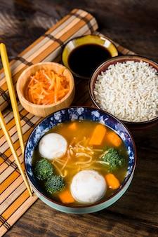 Una vista dall'alto di zuppa di pesce palla con riso e salse su placemat