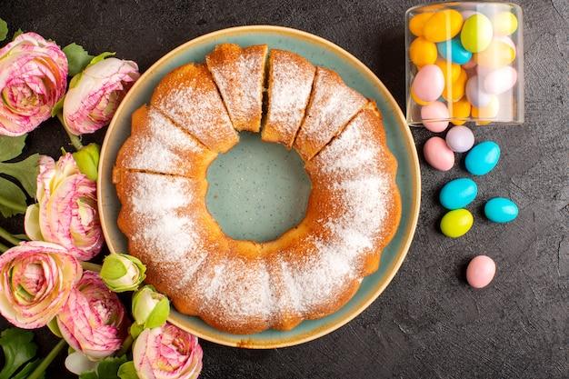 Una vista dall'alto dolce torta rotonda con zucchero in polvere insieme a caramelle colorate a fette dolce delizioso dolce isolato all'interno della piastra e sfondo grigio biscotto zucchero biscotto