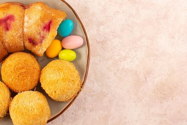 Una vista dall'alto fette di torta di ciliegie con caramelle e biscotti sullo zucchero rosa biscotto torta scrivania