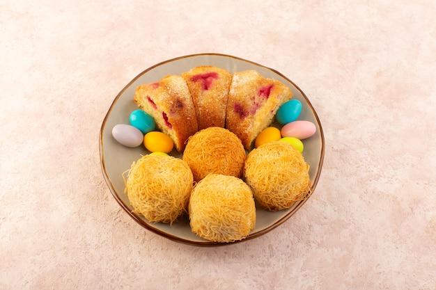 Una vista dall'alto fette di torta di ciliegie con caramelle sullo zucchero rosa biscotto torta scrivania dolce
