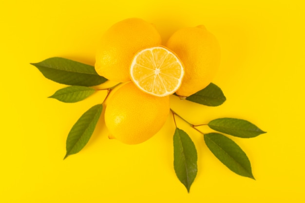Una vista dall'alto giallo fresco limoni freschi maturi interi e affettati insieme con foglie verdi frutti isolati su sfondo giallo colore di agrumi