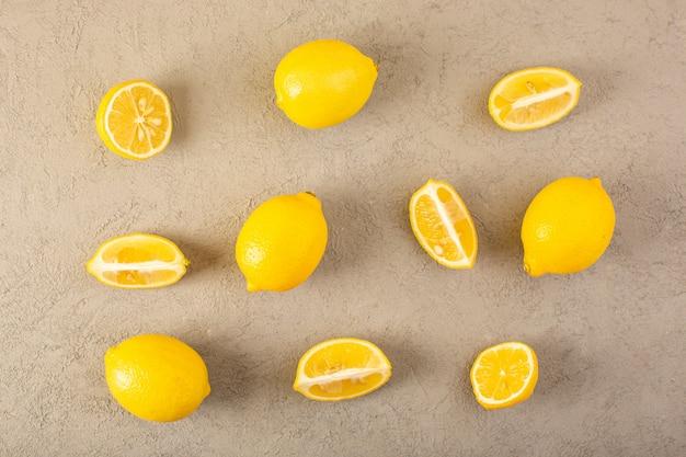 Una vista dall'alto giallo limoni freschi maturi morbidi e succosi interi e affettati allineati sullo sfondo grigio frutti agrumi di colore