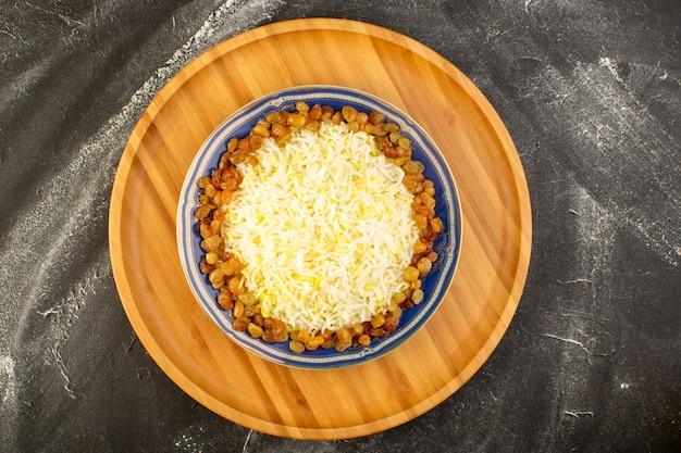 Una vista dall'alto gustoso pilaf con olio e uvetta essiccata all'interno del piatto sulla superficie scura