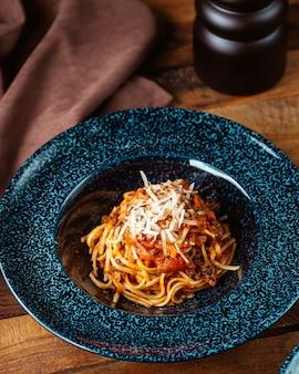 Una vista dall'alto ha cucinato la pasta all'interno del piatto sulla cena del pasto di pasta da tavola marrone