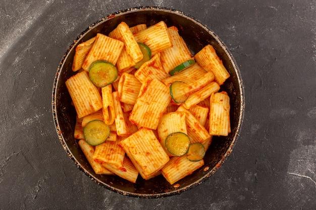 Una vista dall'alto ha cucinato la pasta italiana con salsa di pomodoro e cetriolo all'interno della padella sulla pasta italiana del pasto dell'alimento della tavola scura