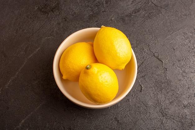 Una vista dall'alto limoni freschi acerbi maturi all'interno bianco piatto intero agrume dolce tropicale giallo vitamina sulla scrivania scura