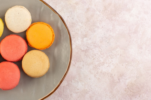 Una vista dall'alto macarons francesi all'interno del piatto sullo zucchero rosa biscotto torta da tavola dolce