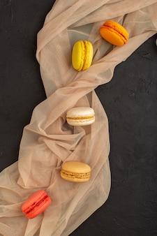 Una vista dall'alto macarons francesi colorati deliziosi e cotti al forno sullo zucchero scuro del biscotto della torta della tavola dolce