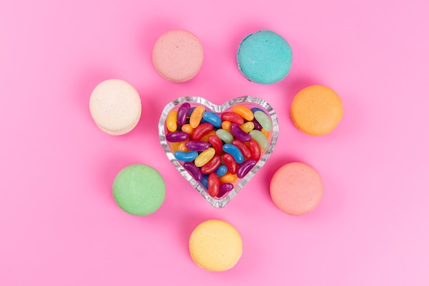 Una vista dall'alto macarons francesi rotondi allineati insieme a caramelle da masticare su rosa, zucchero dolce per torta