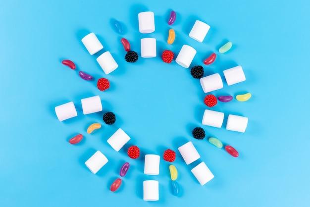 Una vista dall'alto marshmallow e marmellate allineate su un cerchio blu, confetteria di zucchero