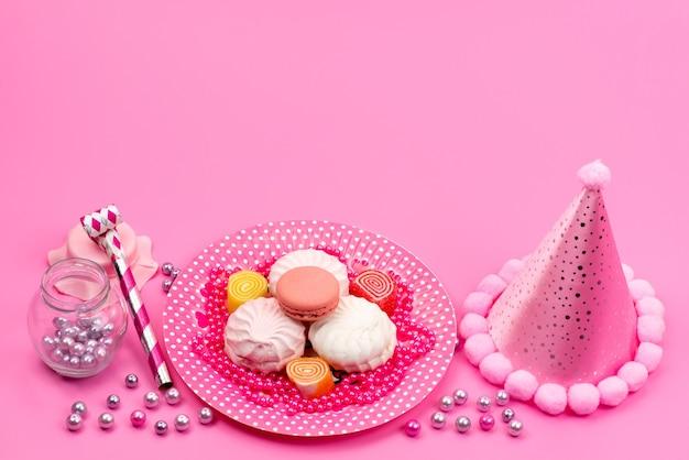 Una vista dall'alto meringhe e macarons dolci e deliziose torte all'interno della piastra con tappo di compleanno e fischietto di compleanno su rosa, biscotto cakek