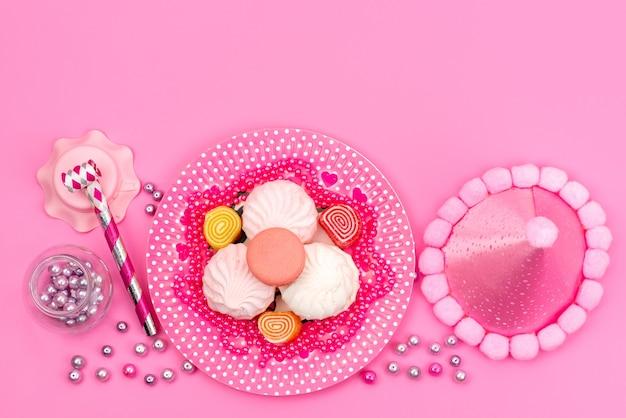 Una vista dall'alto meringhe e marmellate colorate insieme a fischietto di compleanno e collana in rosa, torta di zucchero dolce