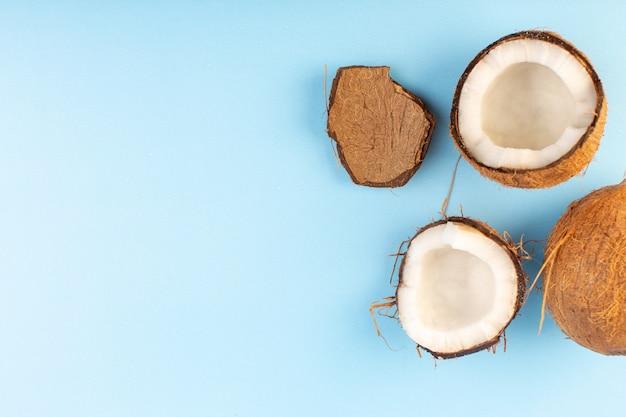 Una vista dall'alto noci coco affettato e intero latteo fresco dolce isolato sul blu ghiaccio