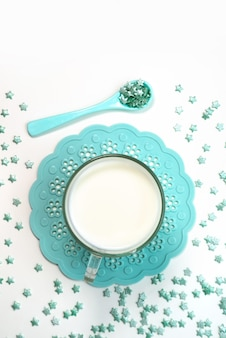 Una vista dall'alto piccole caramelle stella insieme a una tazza di latte su bianco, bere caramelle colorate