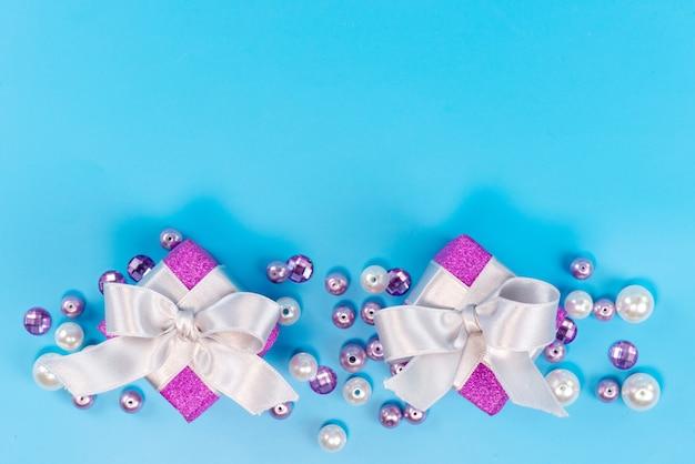 Una vista dall'alto piccole scatole viola per il compleanno isolato sul blu, festa di compleanno