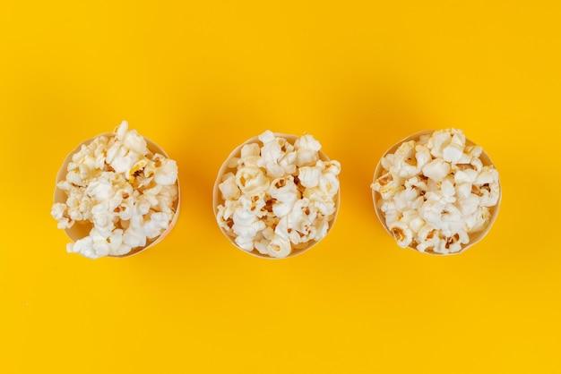 Una vista dall'alto popcorn fresco salato e gustoso su giallo, semi di mais spuntino