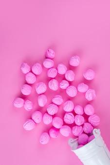 Una vista dall'alto rosa, caramelle deliziose sul colore rosa, zucchero candito dolce