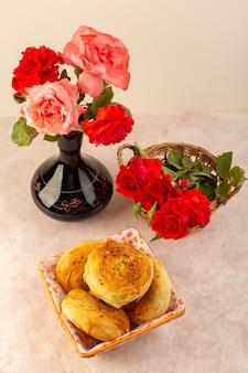 Una vista dall'alto rose rosse bellissimi fiori rosa e rossi all'interno della brocca nera insieme a qogals all'interno del cestino del pane isolato sul tavolo e sul rosa