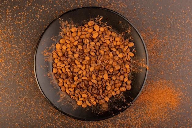 Una vista dall'alto semi di caffè marrone all'interno della banda nera sul tavolo marrone