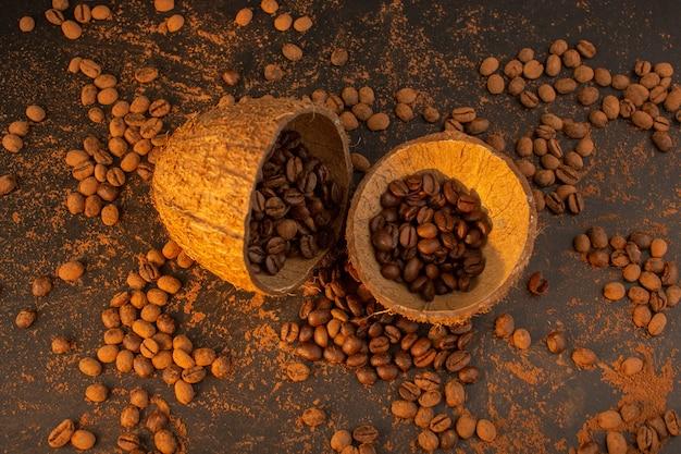 Una vista dall'alto semi di caffè marrone all'interno e all'esterno di gusci di noce di cocco sul granulo marrone del chicco del seme di caffè dello scrittorio