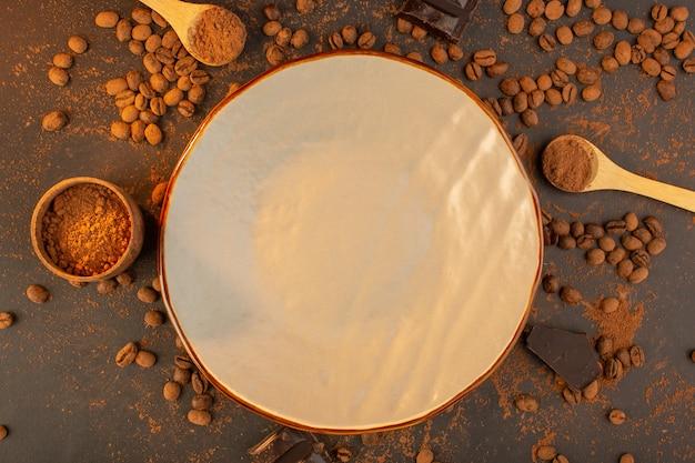 Una vista dall'alto semi di caffè marroni con choco bar in tutto il granello di chicchi di caffè sfondo marrone