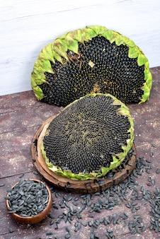 Una vista dall'alto semi di girasole neri freschi e gustosi sullo spuntino marrone del seme di girasole del grano dello scrittorio oleoso