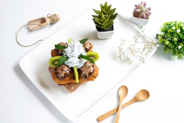 Una vista dall'alto torta al cioccolato progettata con crema pasticcera kiwi a fette all'interno della piastra bianca insieme a piante di decorazione sullo sfondo bianco biscotto biscotto dolce