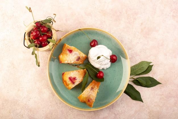Una vista dall'alto torta di frutta al forno deliziosa affettata con ciliegie rosse all'interno e zucchero in polvere all'interno del piatto verde rotondo sul rosa