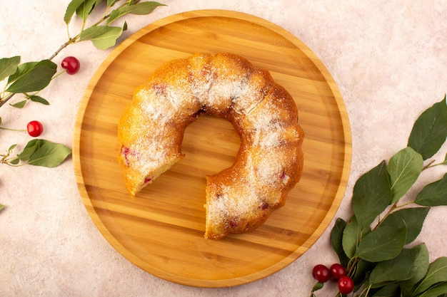 Una vista dall'alto torta di frutta al forno deliziosa affettata con ciliegie rosse all'interno e zucchero in polvere sullo scrittorio rotondo di legno sul colore rosa