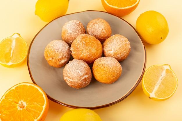Una vista dall'alto torte di zucchero in polvere rotonde dolci deliziose torte al forno all'interno della piattaforma rotonda insieme con arance a fette e limoni sullo sfondo crema biscotto dolce da forno