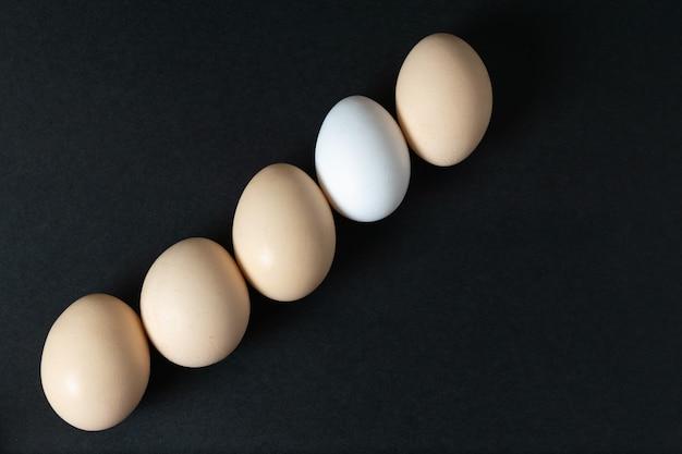 Una vista dall'alto uova bianche intere allineate su oscurità