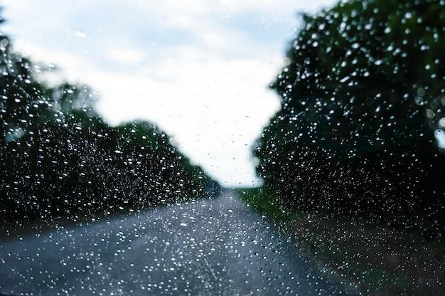 Una vista del tempo piovoso attraverso il parabrezza di un'auto che percorre la strada.