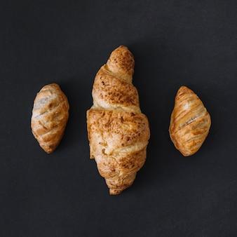 Una vista di alto angolo di tre croissant freschi su priorità bassa nera