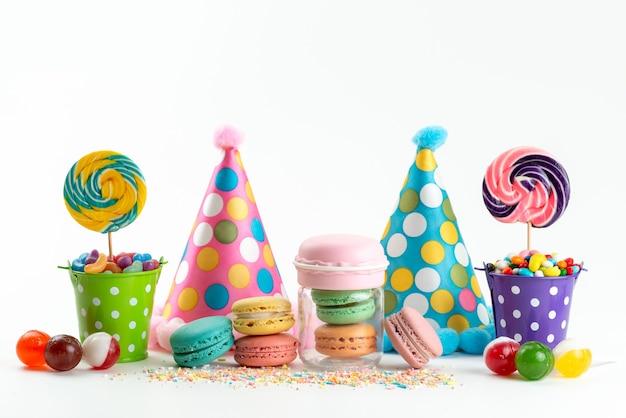 Una vista di fornt deliziosi macarons francesi insieme a caramelle e lecca-lecca di cappelli di compleanno su bianco, biscotto di compleanno di celebrazione