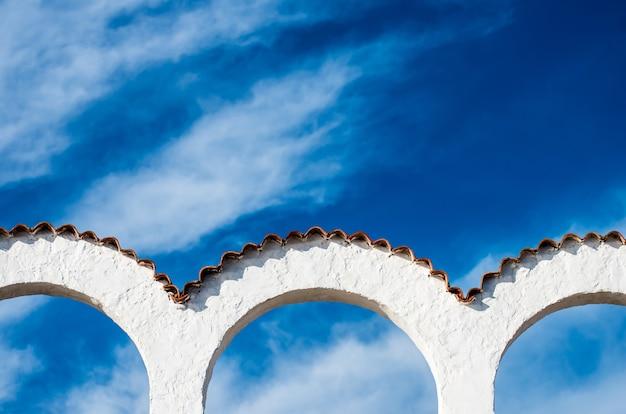 Una vista di tre archi bianchi con le belle nuvole nel cielo blu i