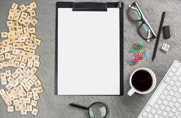 Una vista elevata dei blocchetti di legno della lettera con gli articoli per ufficio sullo scrittorio grigio